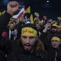 Des partisans du dirigeant du groupe terroriste du Hezbollah, Sayyed Hassan Nasrallah, scandent des slogans avant son discours télévisé dans une banlieue sud de Beyrouth, au Liban, le 5 janvier 2020. (Crédit : Maya Alleruzzo / AP)