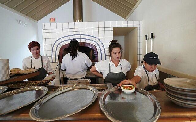 La chef de cuisine Cara Peterson, (à gauche), sa seconde Julia Henner, (deuxième à droite), et la cuisinière de ligne Naomi Martinez (à droite) travaillent au four à pita du restaurant Saba d'Alon Shaya à la Nouvelle-Orléans, le 23 août 2018. (Gerald Herbert/AP)