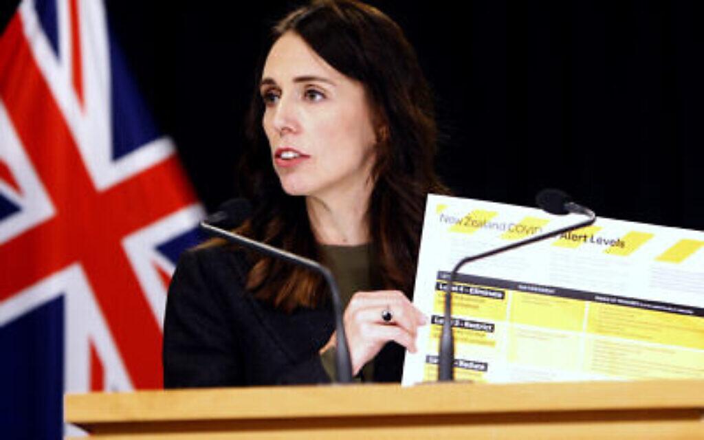 Sur cette photo du 21 mars 2020, la Première ministre néo-zélandaise Jacinda Ardern brandit une carte montrant un nouveau système d'alerte pour le COVID-19 à Wellington, en Nouvelle-Zélande. (AP Photo/Nick Perry)