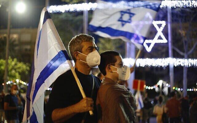 Un couple portant des masques de protection contre la propagation du coronavirus brandit des drapeaux israéliens lors d'une manifestation contre le gouvernement, sur la place Rabin à Tel Aviv, le 2 mai 2020. (AP Photo/Ariel Schalit)
