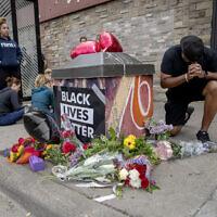 Les gens se rassemblent et prient autour d'un mémorial improvisé, le 26 mai 2020, à Minneapolis, près du site où un homme noir, qui avait été placé en garde à vue la veille, est mort. (Crédit : Elizabeth Flores/Star Tribune via AP)