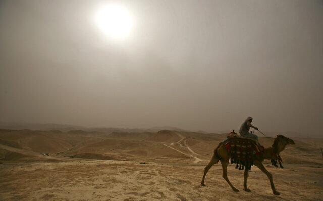 Un Arabe monte son chameau dans la brume aux alentours de la mosquée Nebi Musa, près de la ville de Jéricho, en Cisjordanie, lors d'une vague de chaleur, le 4 mai 2009. (AP Photo/Dan Balilty)