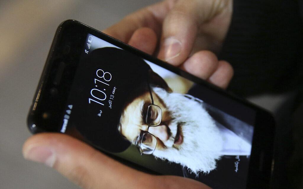 Un résident de Téhéran, Hamed Ghassemi, regarde son téléphone portable, avec un portrait du Guide suprême iranien, l'Ayatollah Ali Khamenei. (AP Photo/Vahid Salemi)