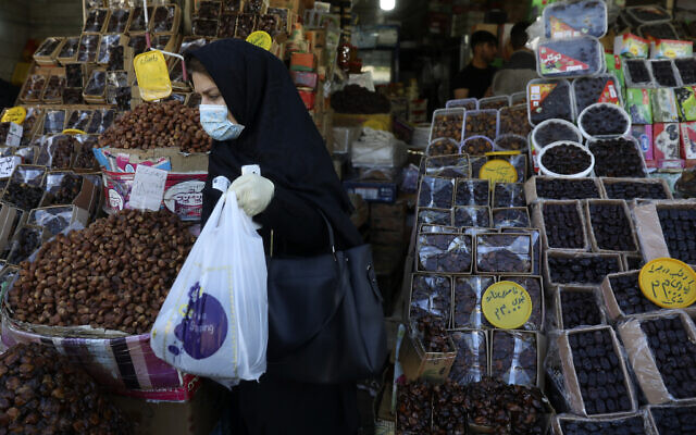 Une femme portant un masque et des gants pour empêcher la propagation du coronavirus fait ses courses pendant le mois sacré du Ramadan à Téhéran, le 27 avril 2020 (Crédit : AP Photo/Vahid Salemi)