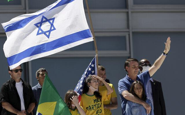 Le président brésilien Jair Bolsonaro, à droite, étreint sa fille alors que des partisans brandissent des drapeaux israélien, brésilien et américain au cours d'une manifestation contre son ex-ministre de la Justice Sergio Moro et contre la Cour suprême devant le palais présidentiel Planalto, à Brasilia, au Brésil, le 3 mai 2020 (Crédit : AP Photo/Eraldo Peres)
