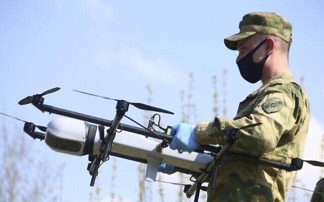 Sur cette photo prise le 3 mai 2020, un soldat de la Rosguardia (Garde nationale) russe se prépare à lancer un drone à Moscou dans le parc national de Losiny Ostrov (Elk Island), au nord-est de la Russie. La police de Moscou a déclaré qu'elle utiliserait des hélicoptères et des drones pour surveiller les violations du confinement destiné à endiguer la propagation du nouveau coronavirus. Les autorités russes signalent une augmentation constante du nombre de nouvelles contaminations par le coronavirus, ce qui augmente la pression sur le système de santé du pays. (Sergey Vedyashkin, Moscow News Agency photo via AP)