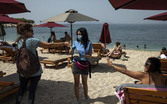 Des baigneurs et une serveuse d'un bar de plage portant un masque de protection contre le coronavirus, à la plage d'Alimos, près d'Athènes, le samedi 16 mai 2020 (Crédit : AP Photo/Yorgos Karahalis)