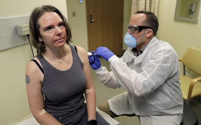 Un pharmacien administre à une volontaire une dose de vaccin lors d'un essai réalisé dans le cadre d'une étude clinique de Phase 1 pour un vaccin anti-Covid-19 mis au point par Moderna Inc. au Permanente Washington Health Research Institute de Seattle, le 16 mars 2020 (Crédit : AP Photo/Ted S. Warren, File)