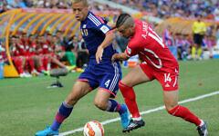 Le Japonais Keisuke Honda, à gauche, et le Palestinien Abdallah Jaber se disputent le ballon lors du match de la Coupe d'Asie de l'AFC entre le Japon et la Palestine à Newcastle, en Australie, le 12 janvier 2014. (Crédit : Rob Griffith/AP)