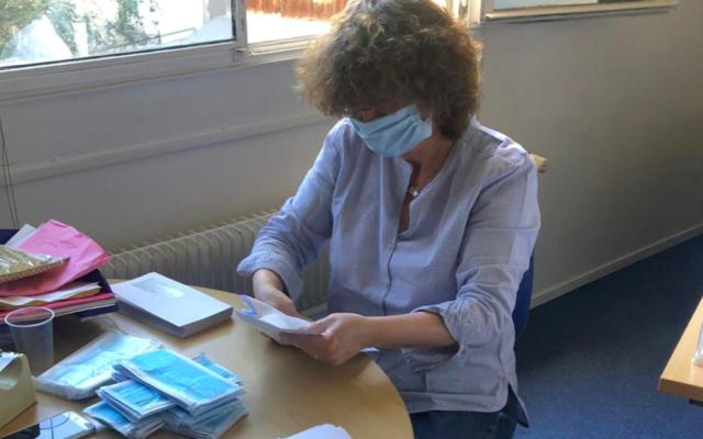 Une bénévole du Fonds social juif unifié prépare les kits de masques envoyés aux survivants de la Shoah. (Crédit : Twitter @fsju)