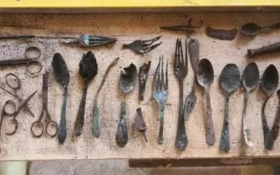 Des cuillères, couteaux, fourchettes et ciseaux cachés dans un conduit de cheminée du bloc 17 du camp de concentration d'Auschwitz en Pologne, retrouvés en avril 2020. (Crédit : Fonds national autrichien pour les victimes du nazisme/Kaczmarczyk/Marszałek)