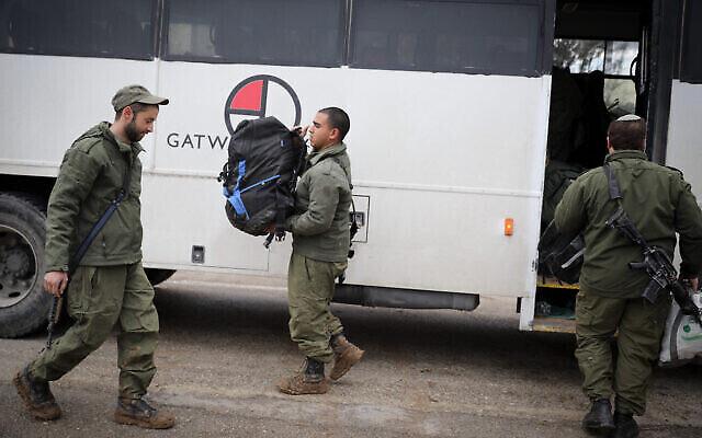 Des soldats israéliens descendent d'un bus arrivé à la frontière avec la bande de Gaza, le 25 mars 2019. (Crédit : Hadas Parush/Flash90)