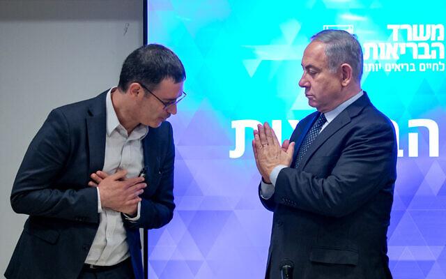 Le Premier ministre Benjamin Netanyahu, à droite, et le directeur-général du ministère de la Santé, Moshe Bar Siman-Tov, lors d'une conférence de presse sur le coronavirus au siège du ministère de la Santé de Jérusalem, le 4 mars 2020 (Crédit : Olivier Fitoussi/ Flash90)