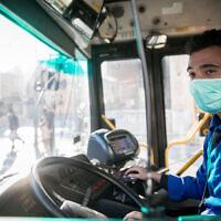 Un chauffeur de bus porte un masque facial par crainte du coronavirus dans le centre-ville de Jérusalem, le 16 mars 2020.(Crédit : Yonatan Sindel/Flash90)