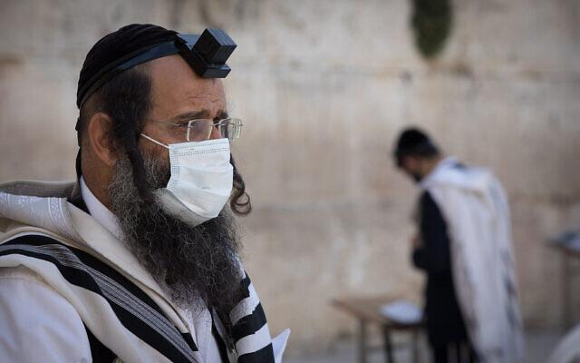 Des hommes juifs prient au Mur occidental, le lieu de prière le plus saint du judaïsme, dans la Vieille Ville de Jérusalem. 19 avril 2020. (Nati Shohat/Flash90)