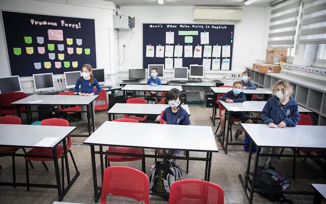 Illustration : Des élèves de l'école primaire portent des masques de protection à leur retour à l'école pour la première fois depuis l'apparition du coronavirus, le 3 mai 2030. (Crédit : Olivier Fitoussi/Flash90)