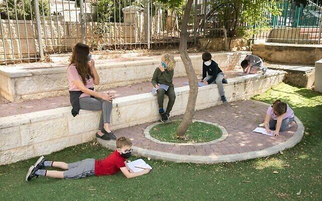 Des élèves israéliens portent des masques pour le premier jour d'école après fermeture à cause de la pandémie de coronavirus, à Jérusalem, le 3 mai 2020. (Crédit : Olviier Fitoussi/Flash90)