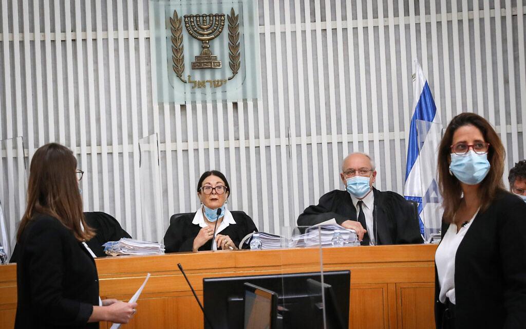 La présidente de la Cour suprême Esther Hayut (au centre) et d'autres juges, portant des masques et avec des séparateurs en plastique transparent entre eux, tiennent une audience pour savoir si Benjamin Netanyahu est éligible pour former le prochain gouvernement d'Israël alors qu'il est mis en accusation, le 3 mai 2020. (Crédit : Yossi Zamir/POOL)