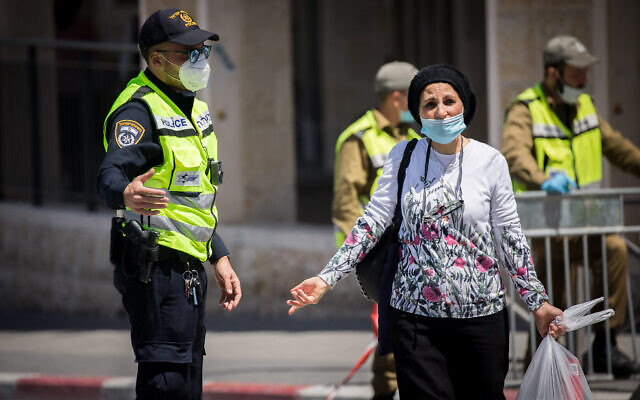 Une femme discute avec un policier à un barrage routier dans le quartier de Romema à Jérusalem, qui est en quarantaine pour empêcher la propagation du coronavirus, le 4 mai 2020. (Yonatan Sindel/Flash90)