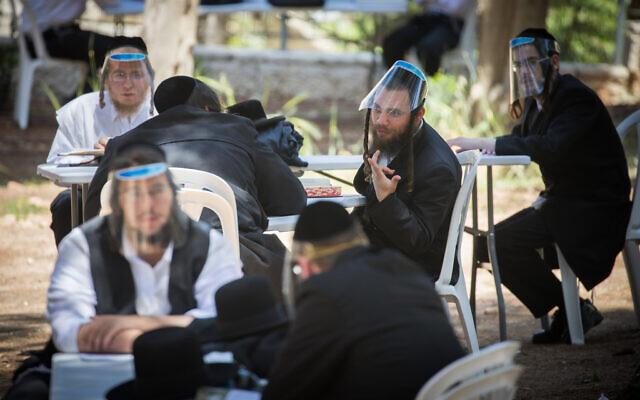 Des hommes ultra-orthodoxes portent des visières de protection comme mesure prise contre le coronavirus, lors d'une étude en plein air à Jérusalem, le 4 mai 2020. (Crédit : Yonatan Sindel/Flash90)