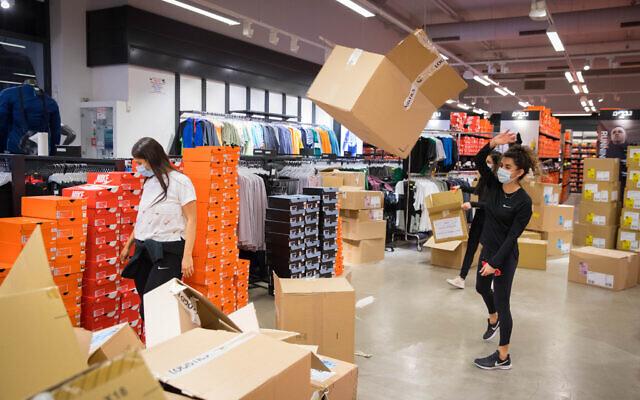 Des employés gantés et masqués préparent la réouverture des magasins du centre commercial Hadar à Jérusalem, le 6 mai 2020. (Crédit : Olivier Fitoussi/FLASH90)