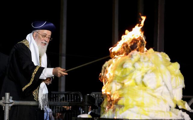 Le grand rabbin séfarade de Jérusalem, le rabbin Shlomo Amar, allume un feu de joie lors des célébrations de la fête juive de Lag BaOmer au mont Meron, dans le nord d'Israël, le 11 mai 2020. (David Cohen/Flash90)