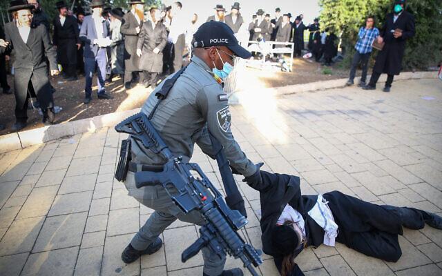 Des hommes ultra-orthodoxes s'affrontent avec des policiers lors des célébrations de Lag B'Omer sur le mont Meron, dans le nord d'Israël, le 12 mai 2020. (Crédit : David Cohen/Flash90)