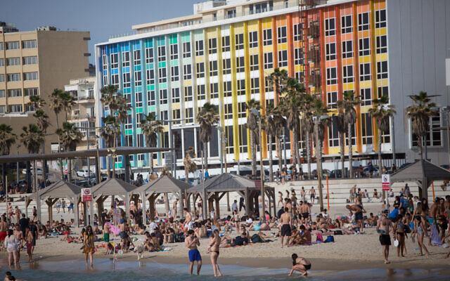 Les Israéliens profitent d'une plage de Tel Aviv, contrevenant aux règles instaurées pour stopper la propagation du coronavirus, le 16 mai 2020 (Crédit : Miriam Alster/FLASH90)
