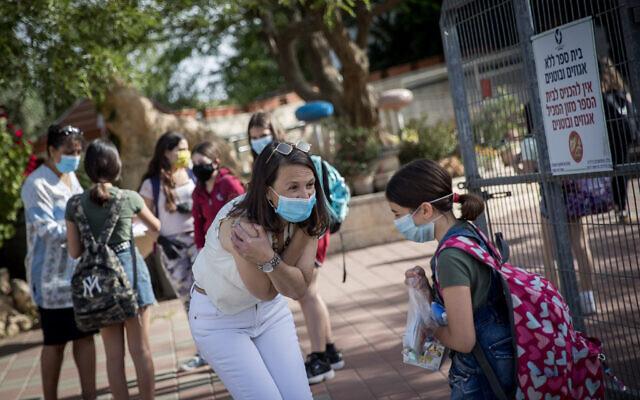 Des élèves et des enseignants portent des masques de protection à leur retour à l'école, à l'école Hashalom de Mevaseret Zion, près de Jérusalem, le 17 mai 2020. (Crédit : Yonatan Sindel/Flash90)