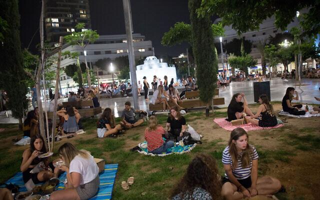 Des Israéliens piquent-niquent sur la place Dizengoff de Tel Aviv, le 20 mai 2020, alors que tous les restaurants, cafés et bars étaient encore fermés sauf pour les livraisons et les plats à emporter dans le contexte de la crainte de la propagation du coronavirus. (Crédit : Miriam Alster/Flash90)