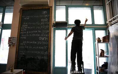 Des membres du personnel du restaurant  Machneyuda préparent la réouverture de l'établissement à Jérusalem, le 25 mai 2020 (Crédit : Olivier Fitoussi/Flash90)