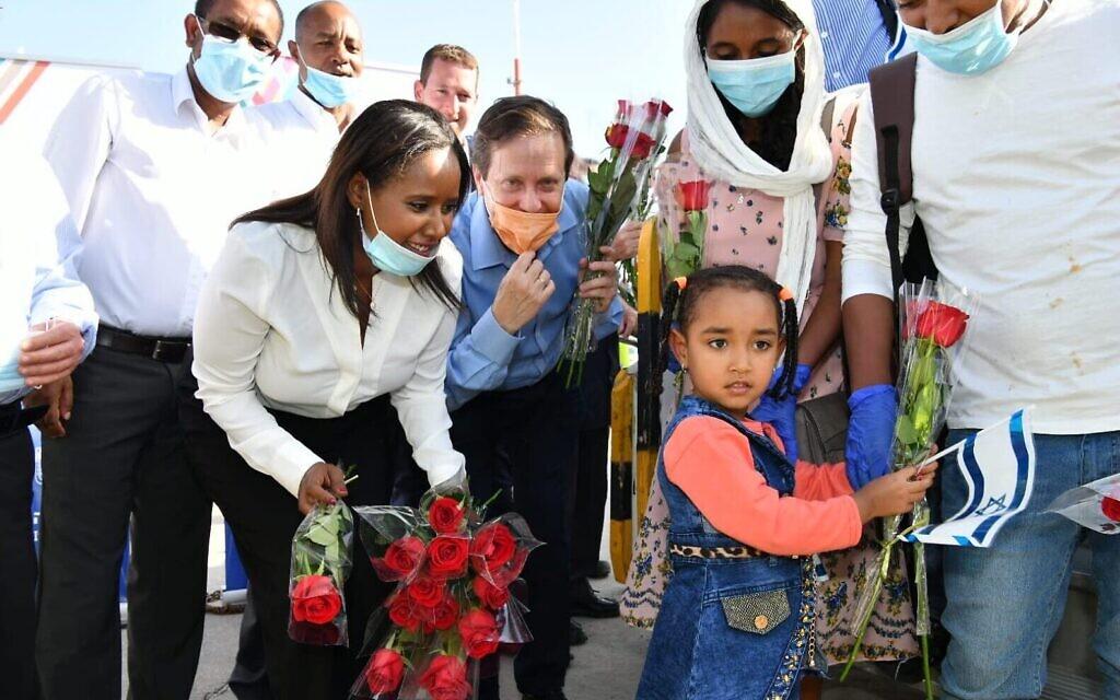 Sur cette photo de l'Agence juive, la ministre de l'Immigration Pnina Tamano-Shata et le dirigeant de l'Agence juive Isaac Herzog saluent 119 immigrants venus d'Éthiopie à l'aéroport Ben Gurion, le 21 mai 2020. (Crédit : Shlomi Amsalem)