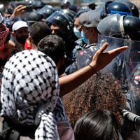 Un manifestant anti-gouvernement affronte les police anti-émeutes pendant une manifestation contre une loi d'amnistie générale proposée au parlement de Beyrouth, le 28 mai 2020 (Crédit : AP/Hussein Malla)