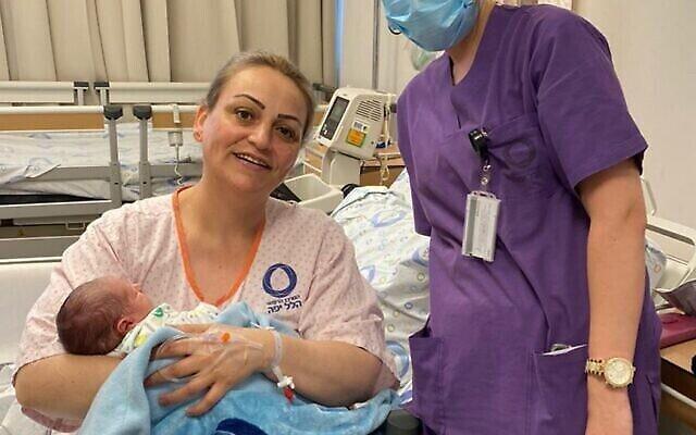 Après 7 ans de traitements pour des problèmes de fertilité et 48 heures de travail, Danit Shipe tient enfin dans ses bras son bébé, né le 72e anniversaire de l'Indépendance d'Israël, le 29 avril 2020. Elle est entourée de la sage-femme Katia Amarna. (Crédit : centre médical Hillel Yaffe)