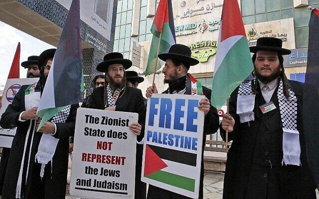 Des hommes juifs ultra-orthodoxes appartenant à Neturei Karta, un petit groupe des Juifs ultra-orthodoxes qui s'opposent à l'existence d'Israël, tiennent des pancartes lors de la manifestation annuelle en mémoire du massacre de 1994 du Tombeau des Patriarches, dans la ville cisjordanienne d'Hébron, le 22 février 2019. (HAZEM BADER / AFP)