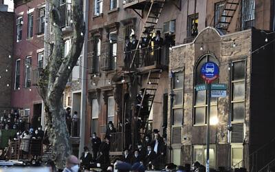 Des résidents du quartier de Williamsburg dans le district de New York sont installés sur des sorties de secours d'incendie alors que des centaines de personnes sont rassemblées le mardi 28 avril 2020 à l'occasion des funérailles du rabbin Chaim Mertz, un rabbin orthodoxe qui serait décédé du COVID-19. (Todd Maisel via AP)