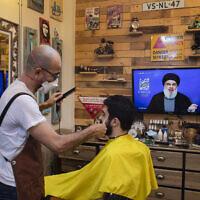 Un barbier portant un masque pour limiter la propagation du nouveau coronavirus écoute un discours du chef du Hezbollah Sayyed Hassan Nasrallah diffusé sur la chaîne de TV du Hezbollah  al-Manar, pour marquer la Journée Al-Quds (Jérusalem) alors qu'il coupe les cheveux d'un client dans son salon situé dans la banlieue sud de Beyrouth au Liban, le vendredi 22 mai 2020. (AP Photo/Hassan Ammar)
