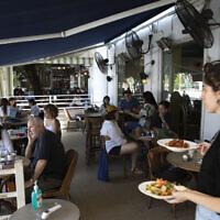 Une serveuse apporte de la nourriture dans un restaurant à Tel Aviv, le mercredi 27 mai 2020. (AP Photo/Sebastian Scheiner)