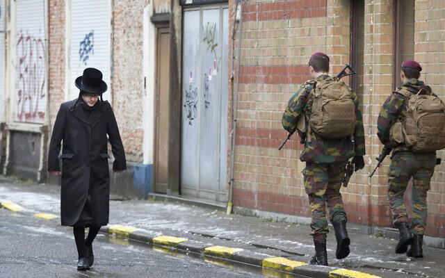 Un enfant juif passe à côté de soldat belges alors qu'is patrouillent lors de services religieux à Antwerp en Belgique, le 24 janvier 2015. (AP Photo/Virginia Mayo)