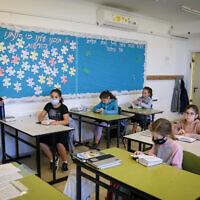 Des élèves israéliens à l'école Orot Etzion à Efrat portent des masques alors qu'ils reviennent à l'école pour la première fois depuis le début de l'épidémie de coronavirus, le 3 mai 2020. (Gershon Elinon/Flash90)