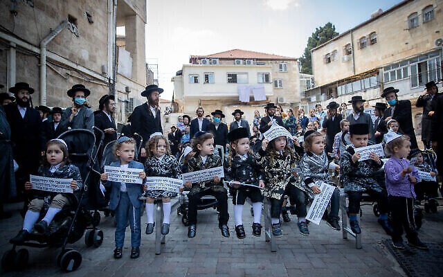 Des hommes juifs ultra-orthodoxes et leurs enfants de trois ans participent à une manifestation contre les restrictions du gouvernement qui les empêchent d'aller au Mont Meron pour Lag BaOmer demain soir, dans le quartier ultra-orthodoxe de Mea Shearim à Jérusalem, le 10 mai 2020. (Photo par Yonatan Sindel/Flash90)