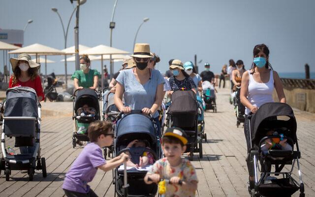 Des Israéliens portent des masques alors qu'ils profitent d'une balade sur le port de Tel Aviv. Le gouvernement a levé certaines mesures de restrictions imposées contre le coronavirus, le 12 mai 2020.  (Miriam Alster/FLASH90)