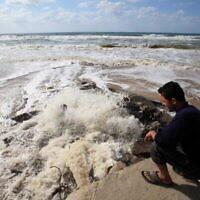 Un Palestinien regarde les eaux usées s'écouler sur la plage, dans le centre de la bande de Gaza, le 22 mars 2010. (Crédit : Wissam Nassar/Flash90)