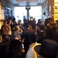 Des dizaines de personnes rassemblées lorsque la police arrive pour disperser la foule qui enfreint la réglementation sur le coronavirus dans une synagogue du quartier ultra-orthodoxe de Mea She'arim à Jérusalem, le 15 mai 2020 (Capture d'écran/Kan)