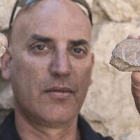 Le Dr Yiftah Shalev de l'Autorité israélienne des Antiquités avec le sceau de l'époque persane et l'empreinte du sceau découverts dans les fouilles du parking Givati de la Cité de David. (Shai Halevy, Autorité israélienne des Antiquités)