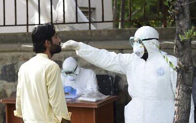 Un membre du personnel médical portant un équipement de protection individuelle (EPI) effectue un test sur un patient suspecté d'être porteur du coronavirus à l'hôpital afghano-japonais des maladies transmissibles de Kaboul, le 9 mai 2020. (Crédit : WAKIL KOHSAR / AFP)