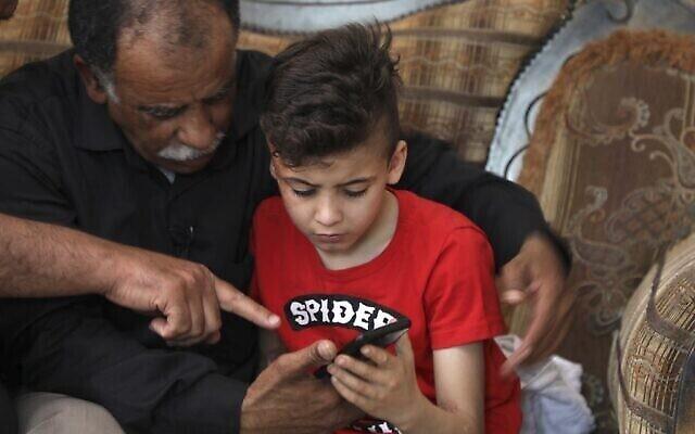 Hussein Dawabsha (à gauche) est assis avec son petit-fils Ahmad, survivant de l'incendie criminel, à leur domicile à Douma, le 18 mai 2020. (JAAFAR ASHTIYEH / AFP)