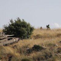 Des soldats libanais et les forces de maintien de la paix regardent le village d'Adaisseh, au Liban, depuis les abords du Kibbutz Misgav Am, alors qu'un tank israélien Merkava fait des manoeuvres près de la ligne de démarcation, le 2 juin 2020 (Crédit : Jalaa Marey/AFP)
