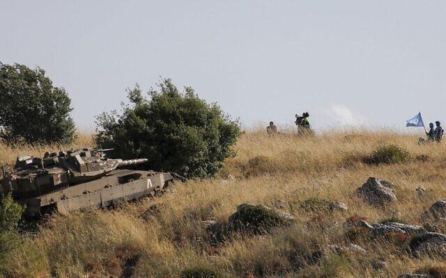 Des soldats libanais et les forces de maintien de la paix regardent le village d'Adaisseh, au Liban, depuis les abords du Kibbutz Misgav Am, alors qu'un tank israélien Merkava fait des manœuvres près de la ligne de démarcation, le 2 juin 2020. (Crédit : Jalaa Marey/AFP)