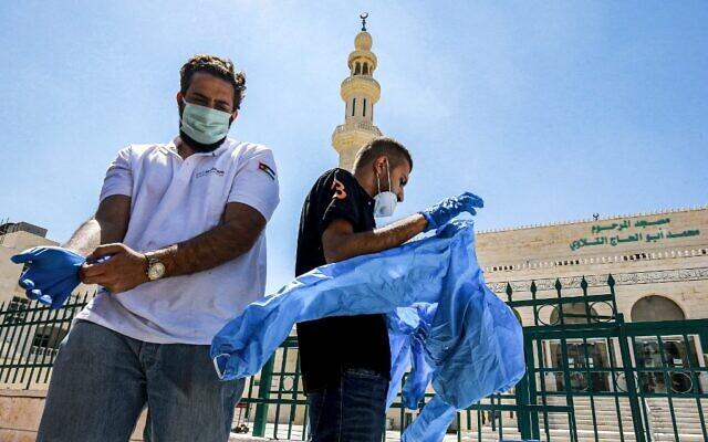 Des travailleurs portent un équipement de protection individuelle avant de stériliser une mosquée à Amman, la capitale de la Jordanie, le 3 juin 2020, avant sa réouverture. (Crédit : Khalil MAZRAAWI / AFP)